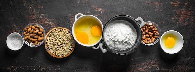 Achtergrond bakken. diverse ingrediënten voor het deeg in kommen. op donkere rustieke achtergrond