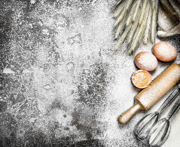 Achtergrond bakken. ingrediënten en hulpmiddelen voor deegbereiding. op een rustieke achtergrond.
