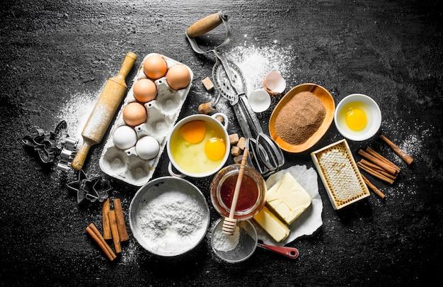 Achtergrond bakken. ingrediënten om thuis koekjes te maken. op zwarte rustieke achtergrond