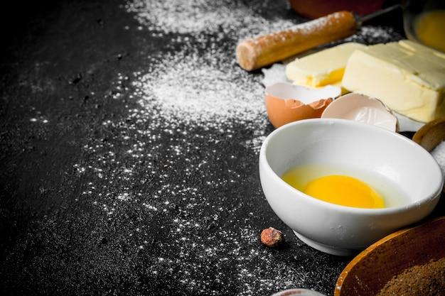 Achtergrond bakken. ingrediënten voor deegbereiding op zwarte rustieke tafel