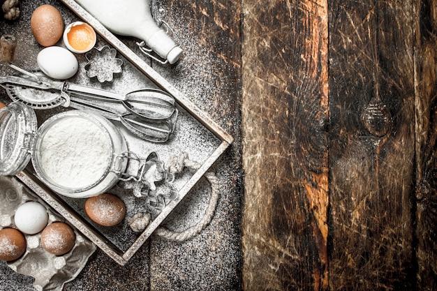 Achtergrond bakken. ingrediënten voor vers deeg. op een houten achtergrond.