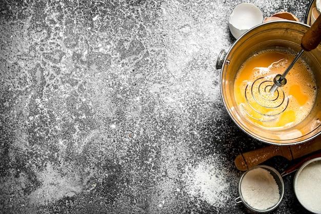 Achtergrond bakken. kloppen van verse eieren in een emmer op rustieke tafel.