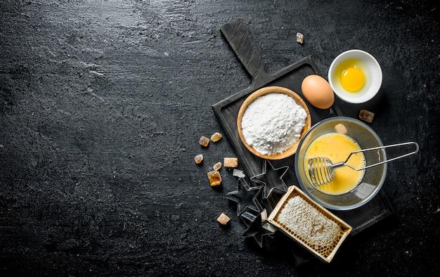 Achtergrond bakken. meel met honing en eieren op de snijplank. op zwarte rustieke achtergrond