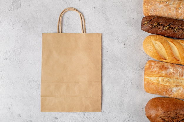 Achtergrond bakken met eco papieren zak uit winkel en broden bovenaanzicht