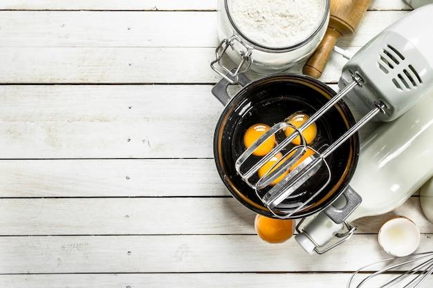 Achtergrond bakken. verse eieren met een mixer. op een witte houten achtergrond.