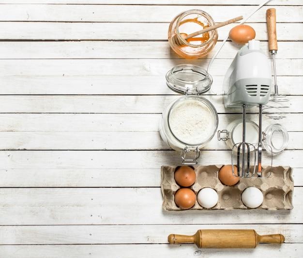 Achtergrond bakken. voorbereiding van deeg voor heerlijke koekjes. op een witte houten achtergrond.