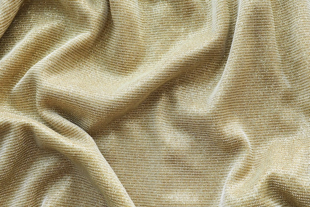 Achtergrond en textuur van een gouden glanzende stof ligt met vouwen.