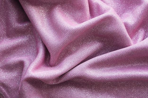 Achtergrond en textuur van een roze glanzende stof ligt met vouwen.
