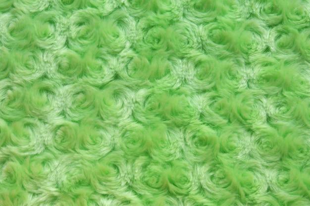 Achtergrond en textuur van felgroen kunstbont met ronde krullen.