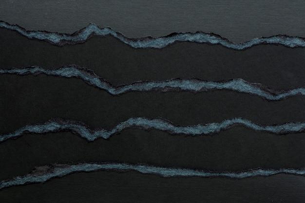 Achtergrond en textuur van verschillende lagen zwart karton met gescheurde randen.