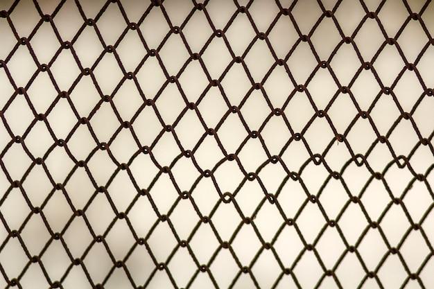 Achtergrond en textuur voor ontwerp. de abstracte textuur van de kettingslink omheining tegen grungy grijze kleurenmuur.