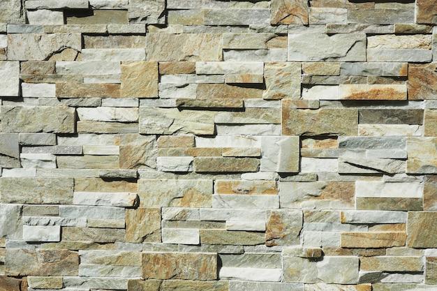 Achtergrond en textuurmuur van steenfragmenten van verschillende grootte. scherpe schaduwen.
