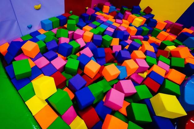 Achtergrond gekleurde zachte kubussen in het droge zwembad, van de kinderkamer van het spel voor verjaardag. uitgaanscentrum. binnenspeeltuin in schuimrubberen bak in trampoline.