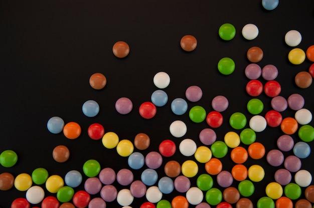 Achtergrond in de vorm van gekleurde kleine blikjes in geglazuurd met een zwarte achtergrond