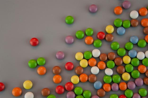 Achtergrond in de vorm van gekleurde kleine blikjes in glazuur op een grijze achtergrond