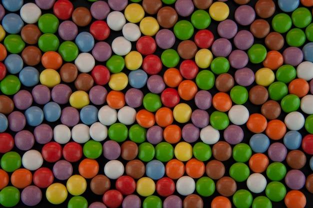 Achtergrond in de vorm van gekleurde kleine blikjes in glazuur op een zwarte achtergrond