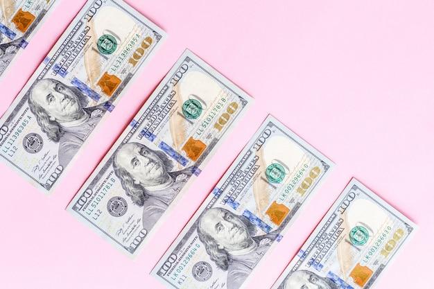 Achtergrond met amerikaanse honderd die dollarsrekeningen van het contant geldgeld op roze worden geïsoleerd. plat leggen. bovenaanzicht