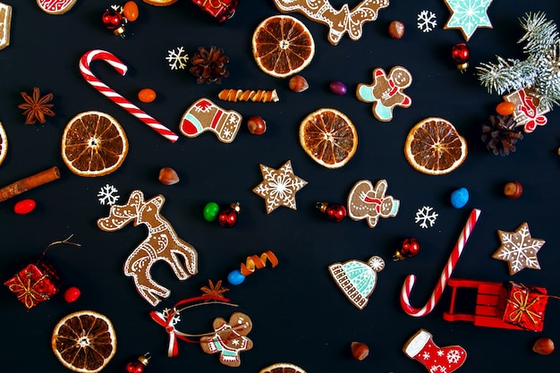 Achtergrond met ballen, kerstkoekjes, sneeuwvlokken en sinaasappels. kerst patroon.