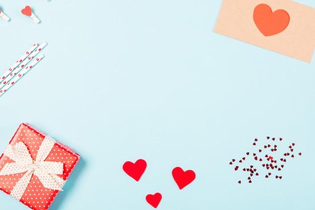 Achtergrond met cadeau, confetti, harten en envelop met vrije ruimte voor tekst op pastel blauwe achtergrond. valentijnsdag concept.