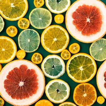 Achtergrond met citrusvruchtencirkelplakken - sinaasappel, mandarijn, limoen, grapefruit op groene achtergrond.