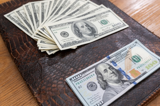 Achtergrond met contant geld amerikaanse honderd-dollarbiljetten laptop telefoon en documenten plat lag bovenaanzicht