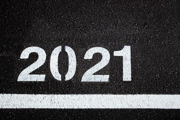 Achtergrond met de letters van het nieuwe jaar 2021 op stedelijk asfalt.
