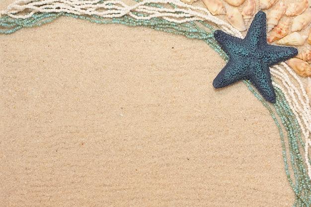 Achtergrond met een blauwe zeester, schelpen en parels