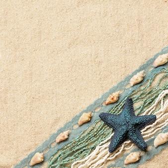Achtergrond met een blauwe zeester, schelpen, linten en parels