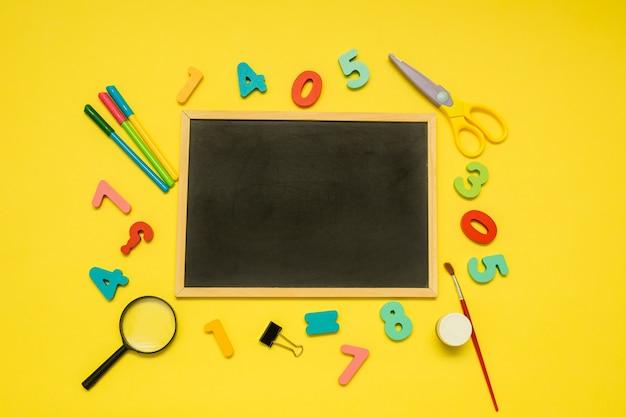 Achtergrond met een lege lei en schoolbenodigdheden op een gele achtergrond