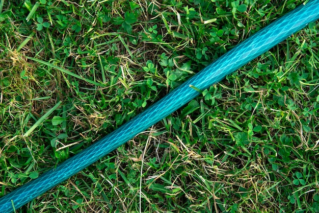 Achtergrond met een tuinslang liggend op het groene gras in de zomer close-up