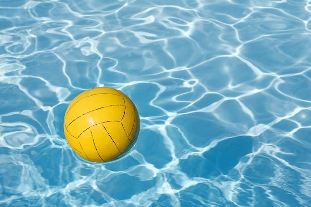 Achtergrond met gele bal in het zwembad en kopieer ruimte