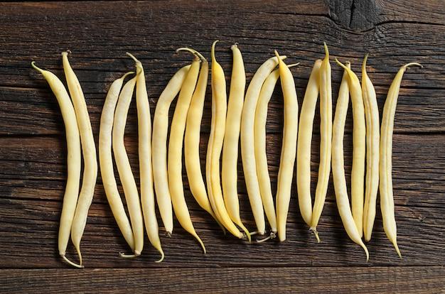 Achtergrond met gele bonen op donkere houten tafel, bovenaanzicht