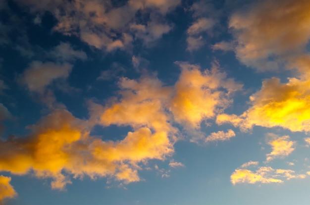 Achtergrond met gele en oranje wolken boven de helderblauwe hemel