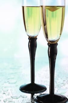 Achtergrond met hoge glazen voor mousserende wijnen. champagne en spray in glazen glazen. feestdrankje met reflectie.