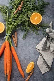 Achtergrond met ingrediënten voor gezonde wortel smoothie met sinaasappel en kaneel.