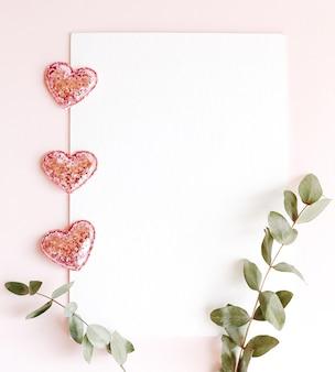Achtergrond met kopie ruimte leeg op roze achtergrond met roze flonkerde harten, eucalyptus tak. witboek bovenaanzicht, plat gelegd, minimalistische stijl. moke-up kaart.