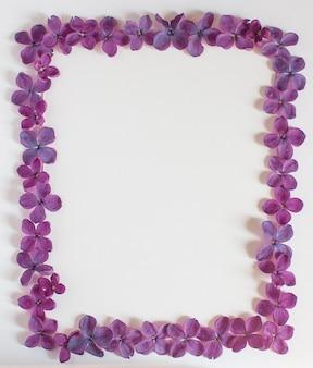 Achtergrond met kopie ruimte leeg op tafel met lila paarse bloem. violette bloemen. witboek bovenaanzicht, plat lag, minimalistische stijl. moke-up kaart.