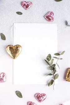 Achtergrond met kopie ruimte leeg op witte tafel met glitter hart, eucalyptus tak, bloemen en bladeren. witboek bovenaanzicht, plat gelegd, minimalistische stijl. moke-up kaart.