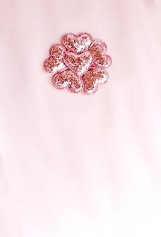 Achtergrond met roze flonkerde harten. roze papieren bovenaanzicht, plat gelegd, minimalistische stijl. moke-up kaart.