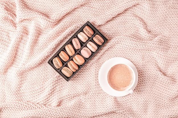 Achtergrond met roze plaid, koffie en bitterkoekjes, bovenaanzicht, kopie ruimte, plat leggen.
