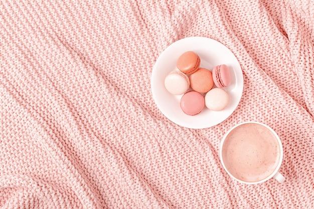 Achtergrond met roze plaid, koffie en bitterkoekjes