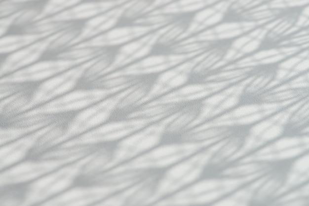 Achtergrond met schaduw van gedessineerde tule valt op witte houten oppervlak