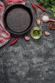 Achtergrond met specerijen, kruiden, olijfolie en pan voor het koken.