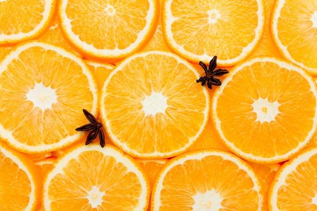 Achtergrond met stukjes sinaasappel, sinaasappels textuur, citrus en anijs.