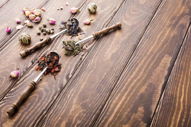 Achtergrond met verschillende soorten theeblaadjes, zwart, groen en aardbei op houten tafel.