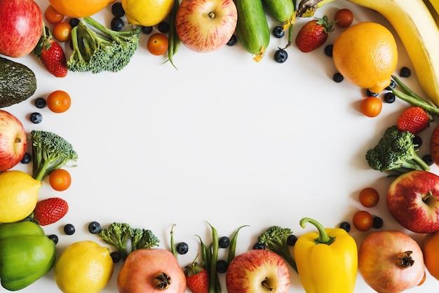 Achtergrond met verse seizoensfruit, groenten en bessen op witte tafel