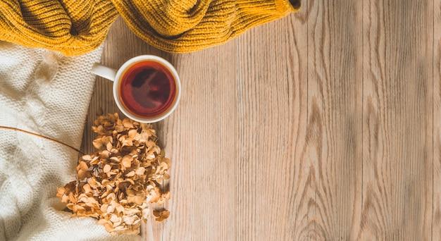 Achtergrond met warme truien en kopje thee. gezellig stilleven in warme tinten. herfst winter concept.