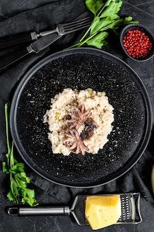 Achtergrond met zelfgemaakte risotto, octopus, champignons, peterselie, sjalotten, parmezaanse kaas en kruiden. bovenaanzicht