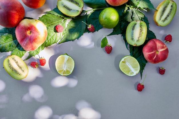 Achtergrond plat lag fruit perzik, kiwi, framboos, limoen op grijs papier, trendy schaduw en zonlicht, zon, minimaal zomerconcept, kopieer ruimte.