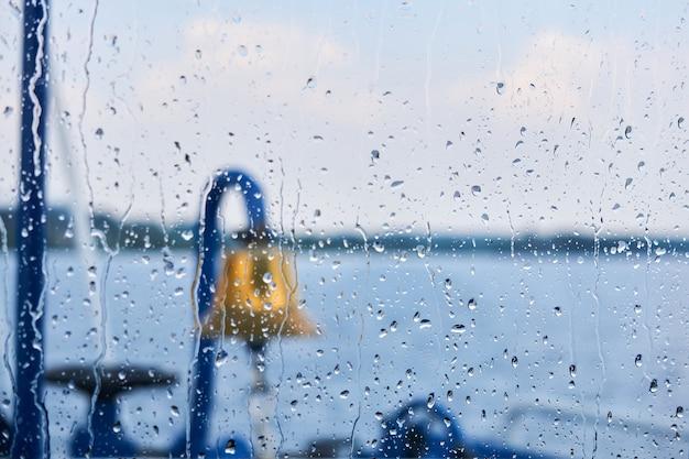 Achtergrond - regendruppels op het glas van de stuurhut, waarachter men een vage bel, andere details van het schip en een regenachtig waterlandschap kan raden